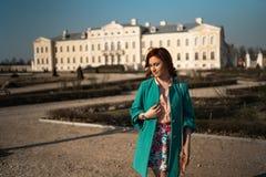 Junge Modeliebhaberfrau, die in einem Park trägt klare grüne Jacke und einen bunten Rock waling ist lizenzfreie stockfotos