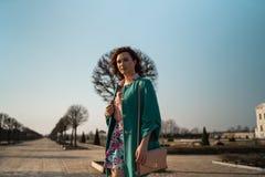Junge Modeliebhaberfrau, die in einem Park trägt klare grüne Jacke und einen bunten Rock waling ist lizenzfreies stockbild