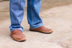 Junge Modemann ` s Beine in den Blue Jeans und braune Stiefel auf concre Stockfotografie