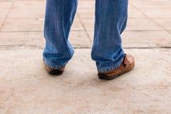 Junge Modemann ` s Beine in den Blue Jeans und braune Stiefel auf concre Stockbild