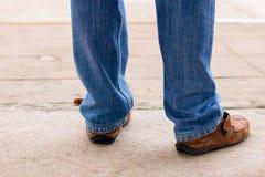 Junge Modemann ` s Beine in den Blue Jeans und braune Stiefel auf concre Lizenzfreie Stockfotos