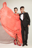 Junge Modepaare, die auf grauem Studiohintergrund aufwerfen Stockfotografie