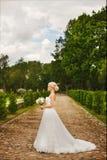 Junge moderne Braut, schönes blondes vorbildliches Mädchen mit stilvoller Hochzeitsfrisur, im weißen Spitzekleid, das draußen auf lizenzfreies stockfoto