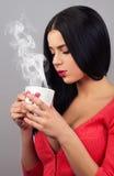 Junge moderne Frau, die heißes Getränk trinkt Lizenzfreie Stockbilder