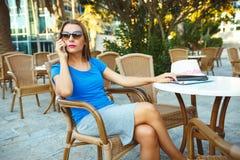 Junge moderne Geschäftsfrau, die am Telefon in einem Café spricht Lizenzfreie Stockfotos