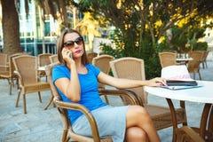 Junge moderne Geschäftsfrau, die am Telefon in einem Café spricht Lizenzfreie Stockfotografie