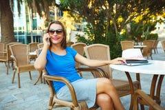 Junge moderne Geschäftsfrau, die am Telefon in einem Café spricht Lizenzfreie Stockbilder