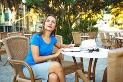 Junge moderne Geschäftsfrau macht Anmerkungen in einem Notizbuch in einem Café Stockfoto