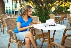 Junge moderne Geschäftsfrau macht Anmerkungen in einem Notizbuch in einem Café Lizenzfreies Stockfoto