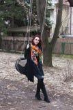 Junge moderne kaukasische Frau Haltung des schwarzen Mantels und des bunten Schals in der im Freien auf Schwingen im Park lizenzfreie stockbilder