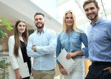 Junge moderne Kollegen in der intelligenten Freizeitkleidung, welche die Kamera steht im kreativen Büro betrachtet stockfoto