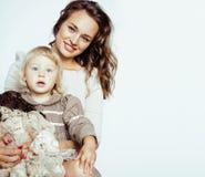 Junge moderne lächelnde blonde Mutter mit kleiner netter Tochter auf w Stockfoto