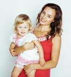 Junge moderne lächelnde blonde Mutter mit kleiner netter Tochter auf w Stockbild