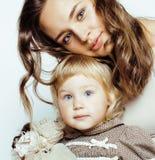 Junge moderne lächelnde blonde Mutter mit kleiner netter Tochter auf w Stockfotografie