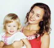 Junge moderne lächelnde blonde Mutter mit kleiner netter Tochter auf w Stockfotos