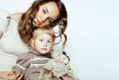Junge moderne lächelnde blonde Mutter mit kleiner netter Tochter auf w Stockbilder