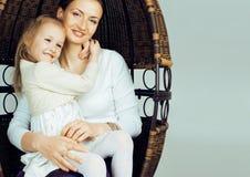 Junge moderne lächelnde blonde Mutter mit kleiner netter Tochter auf w Lizenzfreie Stockfotos
