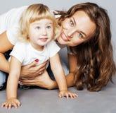 Junge moderne lächelnde blonde Mutter mit kleiner netter Tochter auf w Lizenzfreies Stockfoto