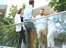 Junge moderne Leute in der intelligenten Freizeitkleidung, die eine Geistesblitzsitzung bei der Stellung hinter der Glaswand im B stockfoto