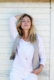 Junge modische Frau, die auf hölzerner Wand steht und sich lehnt Lizenzfreie Stockfotografie