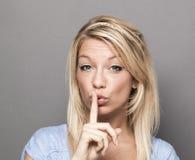 Junge modische Frau, die bittet, für Diskretion auf stille Art zu halten lizenzfreies stockbild