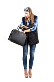 Junge modische Frau, die nach etwas in ihrer Handtasche sucht Stockfotos