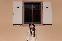 Junge modische Frau steht draußen nahe Fenster stockfotos