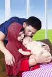 Junge moslemische Eltern küssen ihr Kind Lizenzfreie Stockfotos