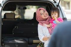 Junge moslemische Familie, Transport, Freizeit, Autoreise und Leutekonzept - glückliche Frau und kleines Mädchen, die am Vater sm lizenzfreie stockfotografie