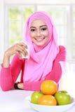 Junge moslemische Frau aß eine Milch und Früchte zum Frühstück Lizenzfreie Stockbilder