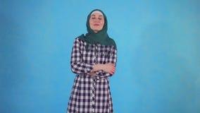 Junge moslemische Frau findet neue Idee auf blauem Hintergrund stock footage