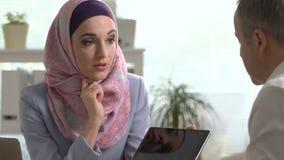 Junge moslemische Geschäftsfrau und kaukasischer Mann, die mit Tablette im Büro arbeitet stock footage