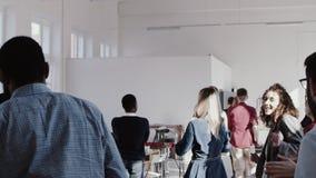 Junge multiethnische Geschäftsleute des glücklichen Spaßes tanzen zusammen an Feierpartei-Zeitlupe des Büros teambuilding ROTEM E stock footage