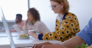 Junge multiethnische Geschäftsleute, die Laptop und digitale Tablette im modernen Büro 4k verwenden stock video