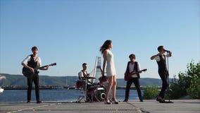 Junge Musiker führen am Pier durch, singen sie und spielen Musikinstrumente stock video footage