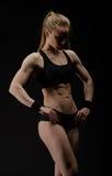 Junge muskulöse Frau, die auf Schwarzem aufwirft Lizenzfreie Stockfotografie