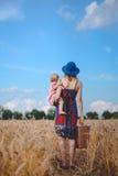 Junge Mutter in den sundress und Hut mit Kind und Stockbilder