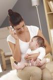Junge Mutter, die auf dem beweglichen Babyaufpassen spricht Lizenzfreie Stockfotografie
