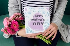 Junge Mutter, die Blumenstrauß von den Gerberagänseblümchen und von Mutter ` s Tagesgrußkarte sitzen auf einer Couch hält lizenzfreie stockfotografie