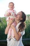Junge Mutter, die draußen mit entzückendem Baby lächelt Lizenzfreie Stockfotos