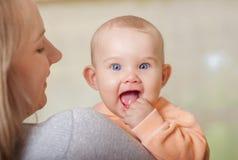 Junge Mutter, die ein Baby hält Lizenzfreie Stockfotografie