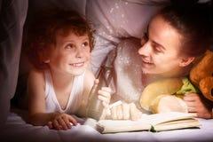 Junge Mutter, die ein Buch zu ihrem reizenden Kind liest Stockfotos
