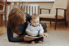 Junge Mutter, die eine Geschichte zu ihrem Säuglingsjungen liest Lizenzfreies Stockbild