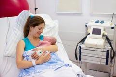 Junge Mutter, die einem Baby entbindet lizenzfreies stockfoto