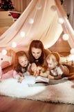 Junge Mutter, die einen Roman mit ihren Kindern liest lizenzfreie stockfotografie