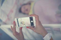 Junge Mutter, die Foto ihres schlafenden Babys macht lizenzfreie stockfotos