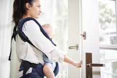 Junge Mutter, die Haus verl?sst lizenzfreies stockfoto