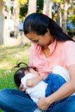 Junge Mutter, die ihr Baby im Park einzieht Stockbild
