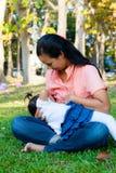 Junge Mutter, die ihr Baby im Park einzieht Stockfoto