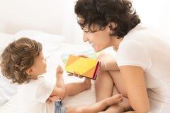Junge Mutter, die ihr Babyfarben beibringt stockfoto